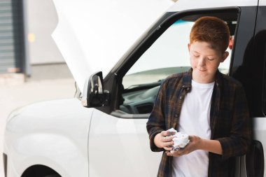 red hair preteen boy repairing car and holding napkin