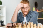Photo handsome pensive red hair man looking at chessboard at home
