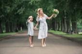 Fotografie matka a dcera v slaměné klobouky s kyticí, drželi se za ruce a chůzi na cestě v zeleném parku