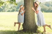 atraktivní matka a šťastná dcera v slaměné klobouky pózuje u stromu na zeleném trávníku