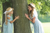 Fotografie smiling mother and daughter in straw hats posing near tree