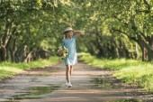 beautiful female child in trendy dress and straw hat holding bouquet of flowers and walking in green orchard