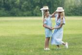 Fotografie Stylový matka a dcera drží slaměné klobouky nad hlavami od sebe