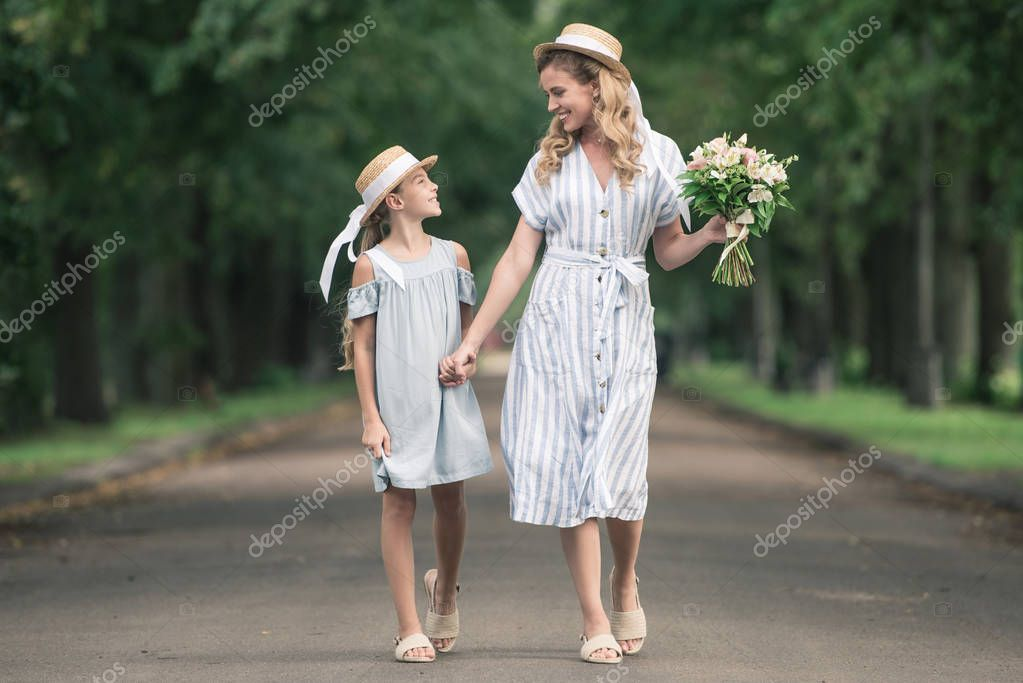 Mother and daughter in straw hats holding hands and walking in green park stock vector