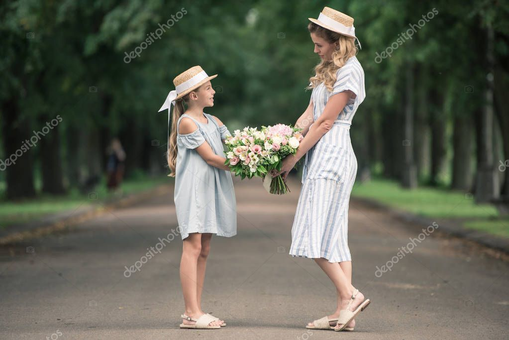 Mom and daughter in straw hats with flower bouquets holding hands in park stock vector