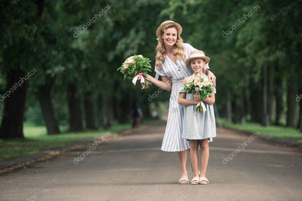 Mom and daughter in straw hats with flower bouquets posing on path in park stock vector