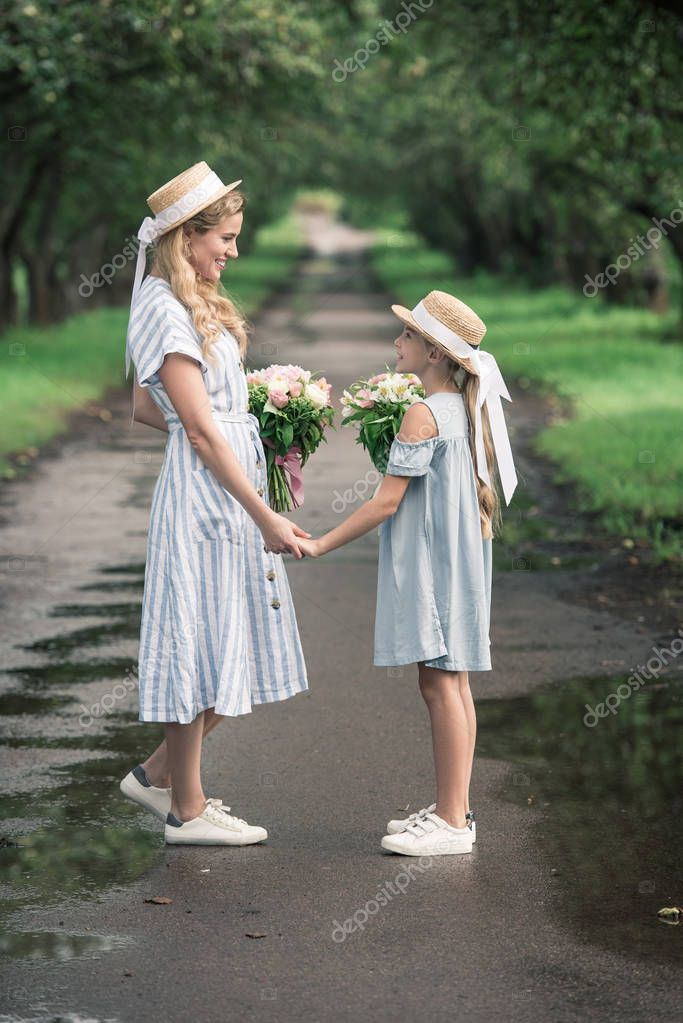 Beautiful mother and daughter in straw hats with flower bouquets holding hands and standing on path in park stock vector