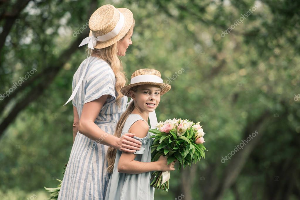 Mom and daughter in straw hats with flower bouquets walking in green park stock vector