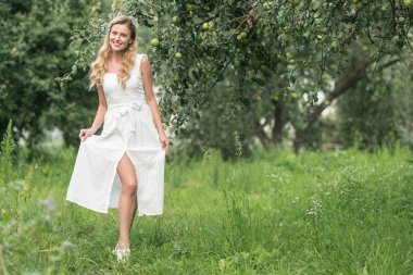 elegant woman in white dress posing in apple orchard