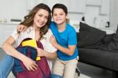mosolygó fiú ölelő anya a könyvet és otthon, hátizsák vissza a concept iskolai portréja
