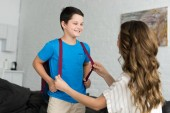 Fotografie partial view of mother and smiling boy with backpack at home, back to school concept