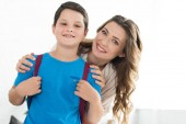 Fotografie portrait of smiling mother and little boy with backpack at home, back to school concept