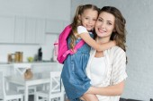 portrait of smiling mother holding little daughter with backpack at home, back to school concept