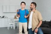 s úsměvem otce a syna s batohem doma, zpět do koncepce školy