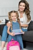 usmívající se matka a s školní potřeby a batoh doma malou dceru, zpět do koncepce školy