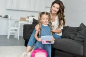 Fotografie smiling mother and little daughter with school supplies and backpack at home, back to school concept