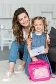 anya és kis lánya a tanszerek és a hátizsák otthon, mosolygó vissza a concept iskolai