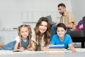 smiling mother and kids looking at camera while doing homework together and man using laptop on sofa at home