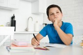 portrait of thoughtful boy doing homework alone at table at home