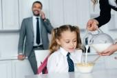 Selektivní fokus kluka ve škole jednotná u stolu se snídaní a matka nalévání mléka do misky s drtí, domů, zpět do koncepce školy
