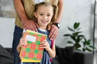 partial view of father and smiling daughter with copybooks in hands at home, back to school concept