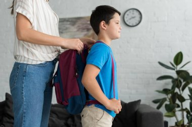 partial view of mother helping son to wear backpack at home, back to school concept