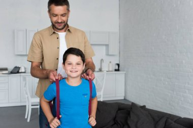 portrait of father helping son to wear backpack at home, back to school concept