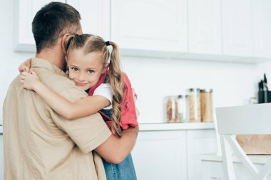 father and little daughter with backpack hugging each other in kitchen at home, back to school concept