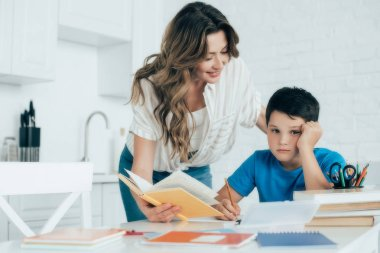 portrait of mother helping bored son with homework at home