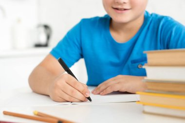partial view of boy writing in copybook while doing homework at home