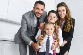 portrait of smiling kids in school uniform with backpacks and parents in suits at home