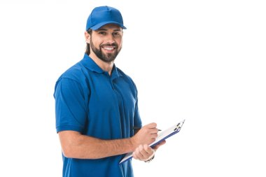 Happy young delivery man writing on clipboard and smiling at camera isolated on white stock vector