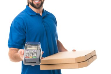 cropped shot of smiling delivery man holding payment terminal and boxes with pizza isolated on white