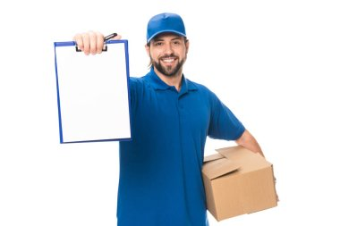handsome happy young delivery man holding cardboard box and blank clipboard isolated on white