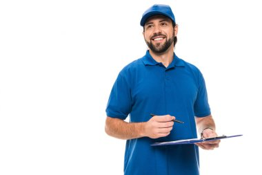 handsome happy delivery man writing on clipboard and looking away isolated on white