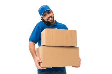 handsome young delivery man holding boxes, talking by smartphone and smiling at camera isolated on white