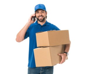 happy young delivery man holding boxes, talking by smartphone and smiling at camera isolated on white