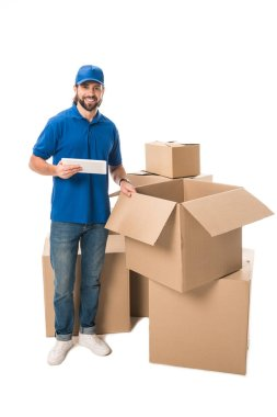 handsome young delivery man using digital tablet and smiling at camera while standing near boxes isolated on white
