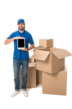 young delivery man holding digital tablet with blank screen and smiling at camera while standing near boxes isolated on white