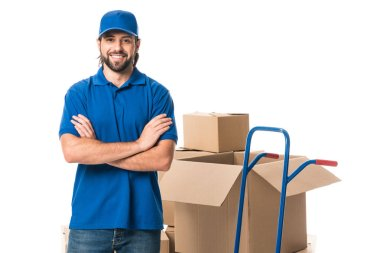 handsome delivery man standing with crossed arms and smiling at camera isolated on white