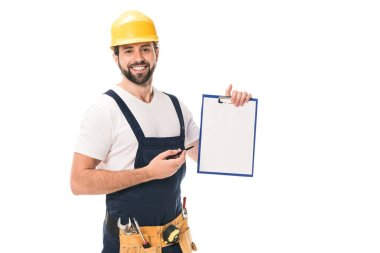 happy construction worker in hard hat and tool belt holding blank clipboard and smiling at camera isolated on white