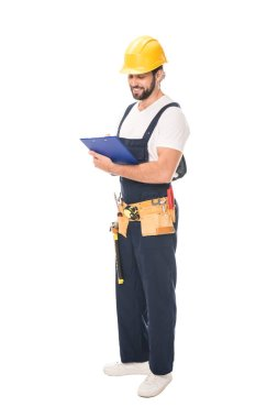 Full length view of smiling workman in tool belt writing on clipboard isolated on white stock vector