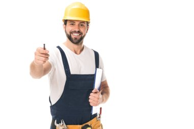 handsome construction worker in hard hat holding clipboard and smiling at camera isolated on white