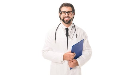 handsome bearded doctor in eyeglasses holding clipboard and smiling at camera isolated on white
