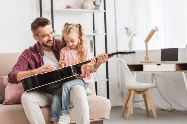father and daughter having fun and playing on guitar on sofa