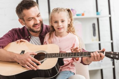 cheerful dad and daughter having fun and playing on guitar