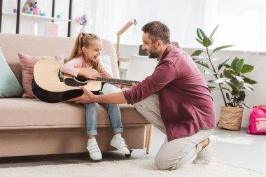 neşeli baba ve kızı eğleniyor ve gitar çalmaya