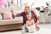 Fotografie otec a dcera v klobouky s selfie s dárkem k narozeninám