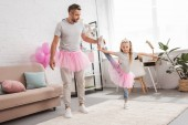 Fotografie father helping daughter to stand on one leg