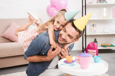 father piggybacking daughter in cone hat while playing tea party at home